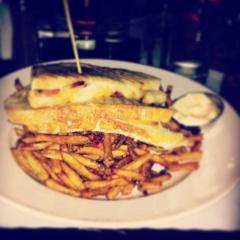 Le grilled-cheese 'Hula Hoop': fondant au cheddar, mozzarella, OKA, bacon, pain grillé et frites maison.